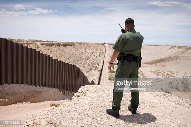 Border Patrol agent watches over the border fence on the US and Mexico border near Sunland Park New Mexico May 20 2014