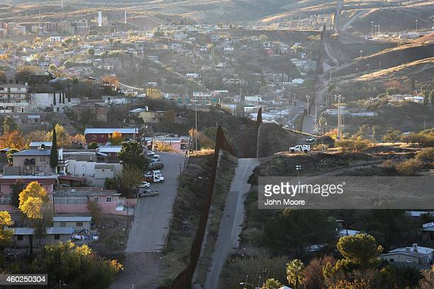 S Border Patrol agent watches over the USMexico border fence from his vehicle on December 9 2014 in Nogales Arizona With increased manpower and...