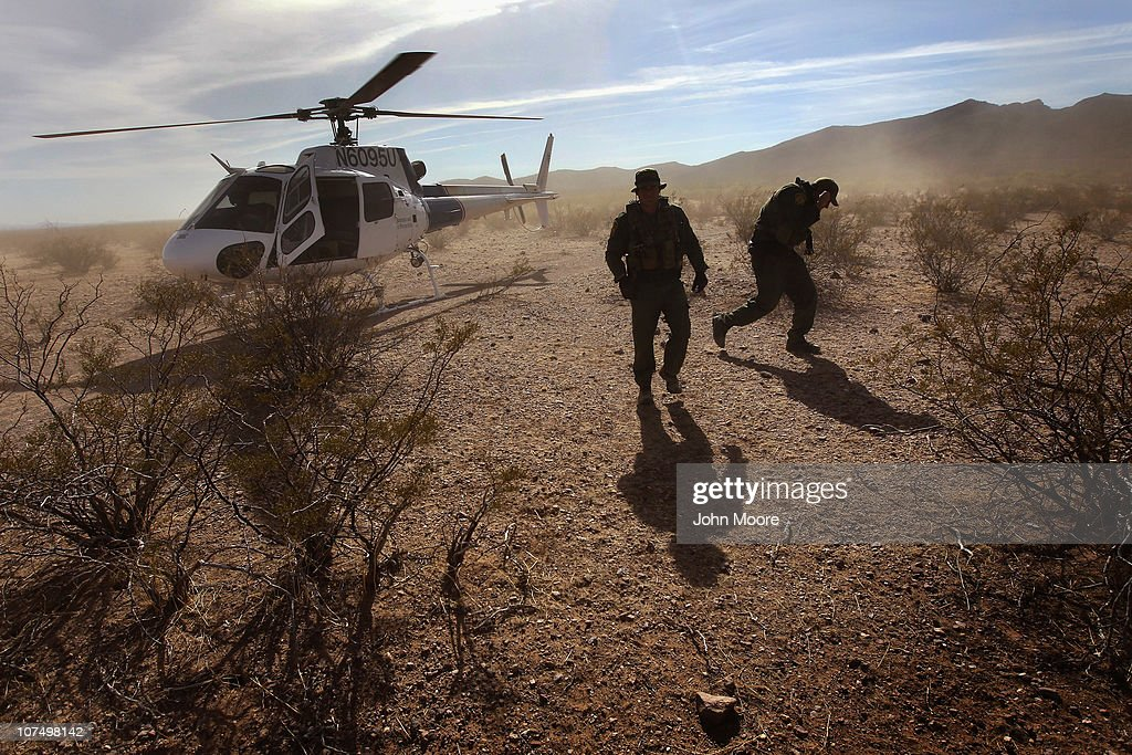 Border Patrol agents deplane a helicopter from the U.S. Office of Air and Marine after searching for drug smugglers spotted in a remote area of the Sonoran Desert on December 9, 2010 in the Tohono O'odham Reservation, Arizona. The area is a favorite spot for smugglers and illegal immigrants to cross the border into the United States.