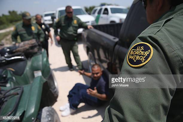 S Border Patrol agents detain a suspected smuggler after he allegedly transported undocumented immigrants who crossed the Rio Grande from Mexico into...