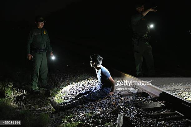 S Border Patrol agents detain an undocumented immigrant along a railroad track near the Rio Grande River at the USMexico border on September 8 2014...