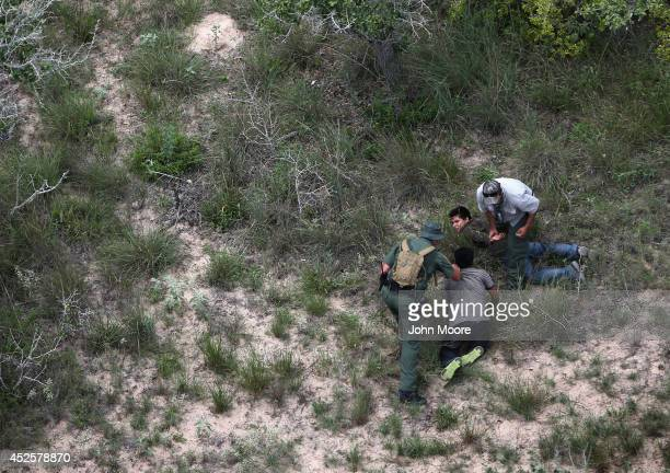 S Border Patrol agents detain undocumented immigrants some 60 miles north of the USMexico border on July 23 2014 near Falfurrias Texas They were part...