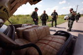 Border Patrol agents examine bales of marijuana in a car near the Mexican border on May 27 2010 near McAllen Texas Agents watched as a car was loaded...