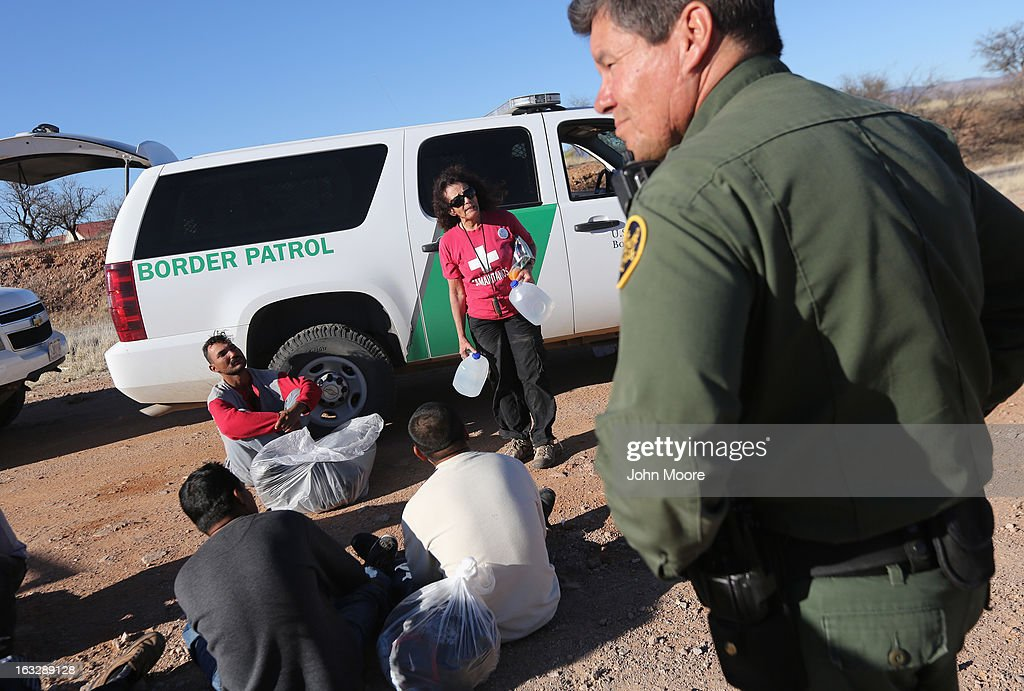 U.S. Border Patrol agents guard a group of Mexican immigrants caught after they crossed illegally into the United States on March 6, 2013 near Walker Canyon, Arizona. Elisa Hauptman, a volunteer for the non-profit Samaritans group, arrived to offer water to the detained immigrants. Due to broad federal sequestration budget cuts, Border Patrol agents are expected to begin taking unpaid furlough days in April, as Customs and Border Protection funding is expected to be reduced by more than $500 million.