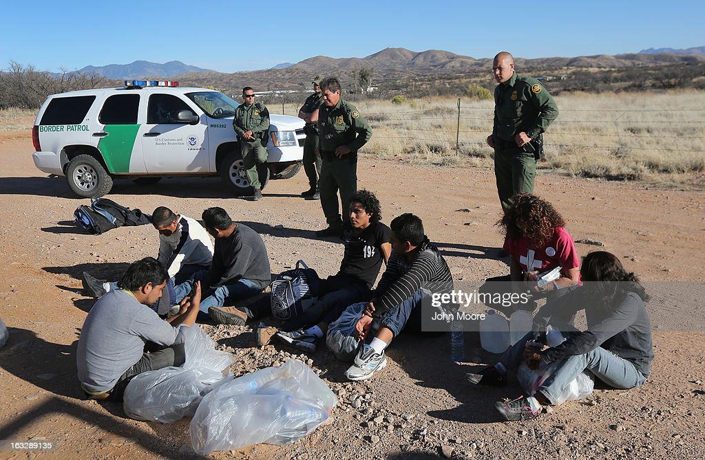 U.S. Border Patrol agents guard a group of Mexican immigrants caught after they crossed into the United States on March 6, 2013 near Walker Canyon, Arizona. Due to broad federal sequestration budget cuts, Border Patrol agents are expected to begin taking unpaid furlough days in April, as Customs and Border Protection funding is expected to be reduced by more than $500 million.