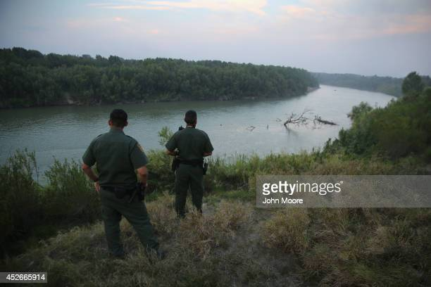 S Border Patrol agents look for immigrants crossing the Rio Grande from Mexico to the United States at dusk on July 24 2014 near Mission Texas Tens...