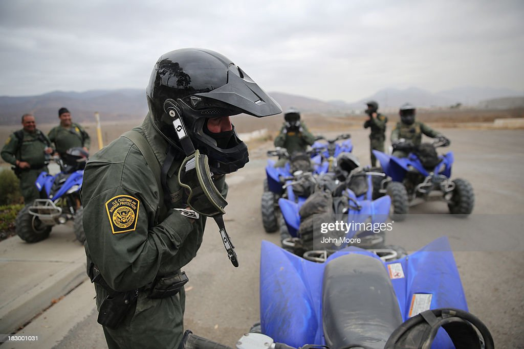 U.S. Border Patrol agents mount their all terrain vehicles near the U.S.-Mexico border on October 3, 2013 near San Ysidro, California. While hundreds of thousands of government workers were furloughed Tuesday, thousands of Border Patrol agents, air-traffic controllers, prison guards and other federal employees deemed 'essential' remain on duty, although their pay may be delayed.