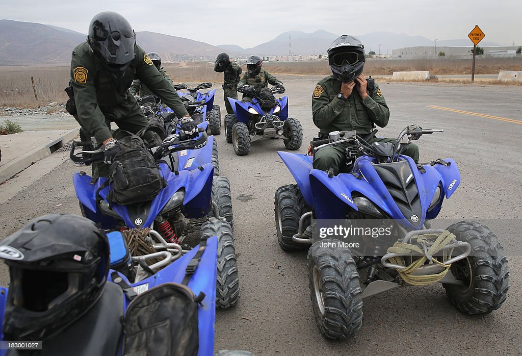U.S. Border Patrol agents mount their terrain vehicles near the U.S.-Mexico border on October 3, 2013 near San Ysidro, California. While hundreds of thousands of government workers were furloughed Tuesday, thousands of Border Patrol agents, air-traffic controllers, prison guards and other federal employees deemed 'essential' remain on duty, although their pay may be delayed.