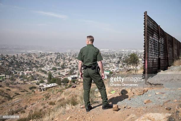 S Border Patrol agents near the USMexico border fence overlooking Tijuana Mexico on May 27 2014 near San Diego California