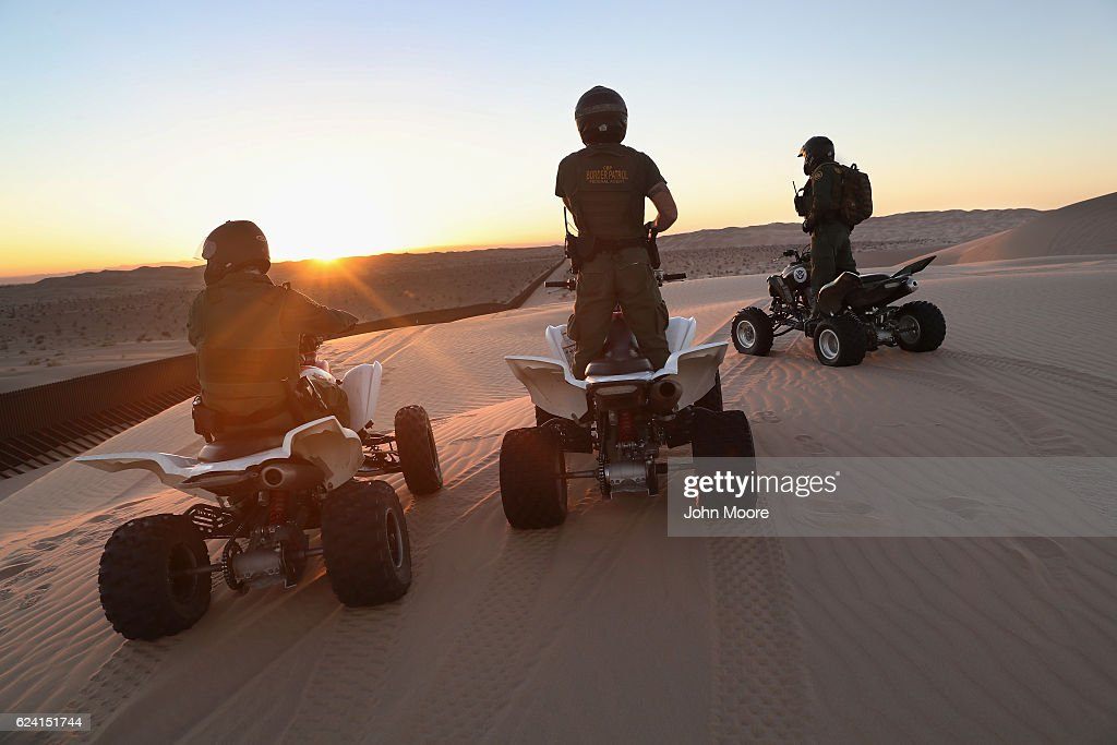 U.S. Border Patrol agents on ATVs monitor the U.S.-Mexico border fence at the Imperial Sand Dunes on November 17, 2016 near Felicity, California. The 15-foot fence, also known as the 'floating fence,' sits atop the dunes and moves with the shifting sands. Border Patrol agents say they catch groups of illegal immigrants and drug smugglers crossing in from Mexico there daily, despite the forbidding terrain.