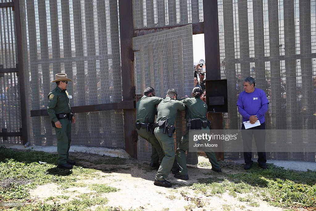 U.S. Border Patrol agents open a door in the U.S.-Mexico Border fence during an 'Opening the Door of Hope' event on April 30, 2016 in San Diego, California. Five families, with some members living in Mexico and others in the United States, were permitted to meet and embrace for three minutes each at a door in the fence, which the U.S. Border Patrol opened to celebrate Mexican Children's Day. It was only the third time the fence, which separates San Diego from Tijuana, had been opened for families to briefly reunite. The event was planned by the immigrant advocacy group Border Angels.