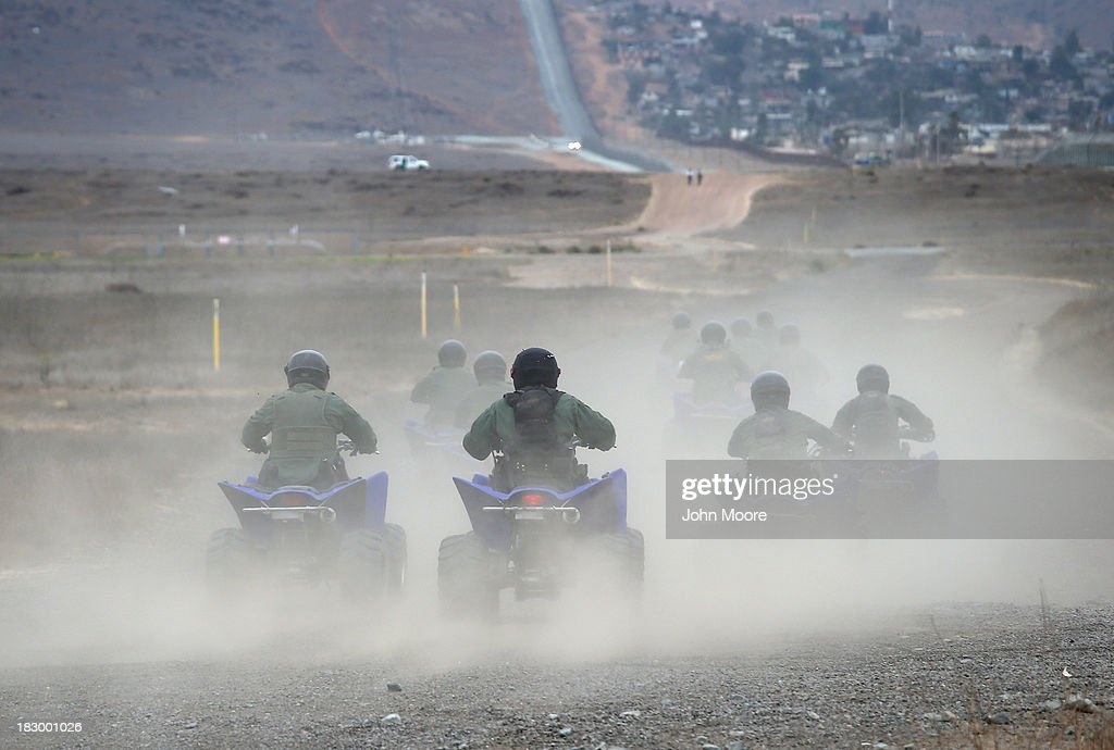 U.S. Border Patrol agents ride all terrain vehicles near the U.S.-Mexico border on October 3, 2013 near San Ysidro, California. While hundreds of thousands of government workers were furloughed Tuesday, thousands of Border Patrol agents, air-traffic controllers, prison guards and other federal employees deemed 'essential' remain on duty, although their pay may be delayed.