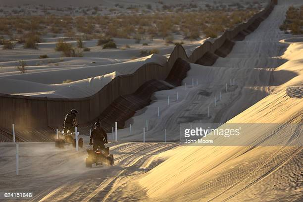 S Border Patrol agents ride ATVs along the USMexico border fence at the Imperial Sand Dunes on November 17 2016 near Felicity California The 15foot...