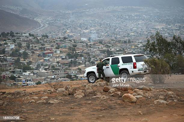 S Border Patrol agents speak near the USMexico border fence overlooking Tijuana Mexico on October 3 2013 near San Diego California While hundreds of...