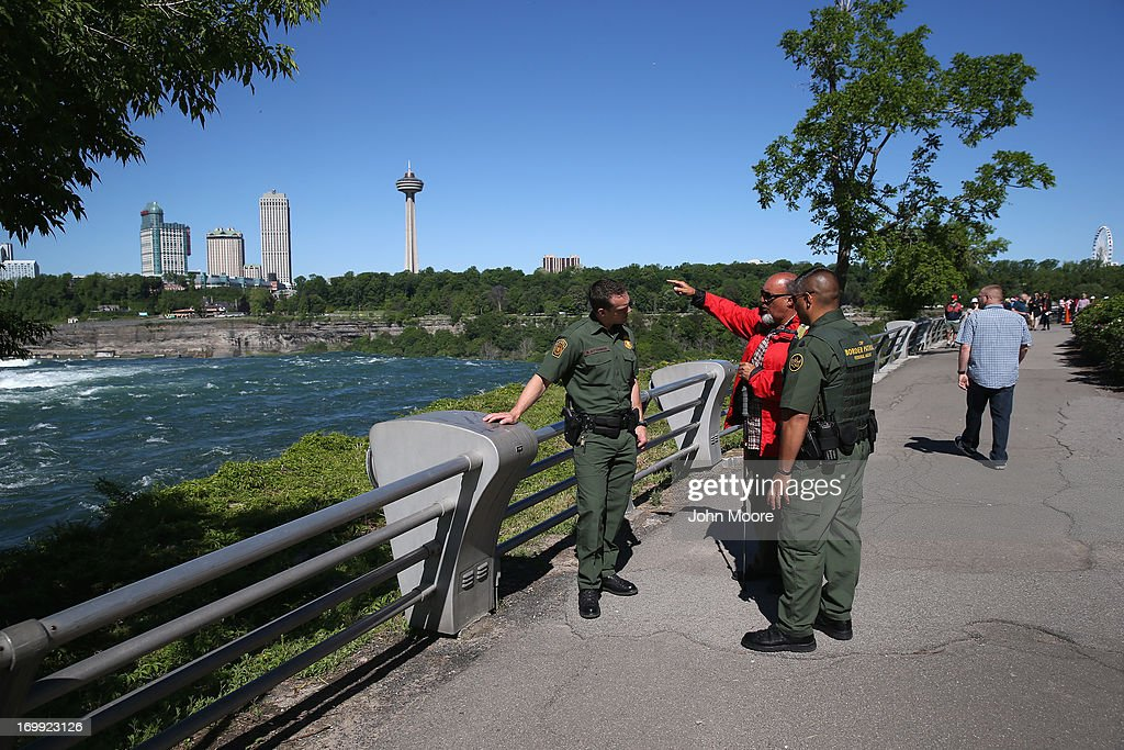 U.S. Border Patrol agents speak with a tourist near Niagara Falls on June 4, 2013 in Niagara Falls, New York. The falls, which lie directly on the U.S.-Canada border, are a major destination for international visitors. Border Patrol agents detain travelers who have overstayed their visas as well as undocumented immigrants who attempt to illegally cross the international bridge in Niagara Falls.