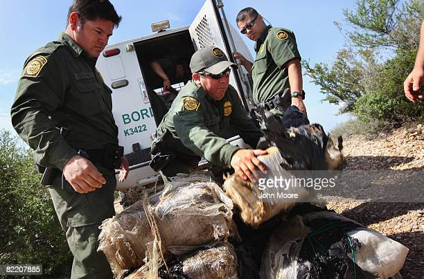 S Border Patrol agents stack more than 400 pounds of marijuana seized from drug smugglers after it was brought across the Rio Grande River from...