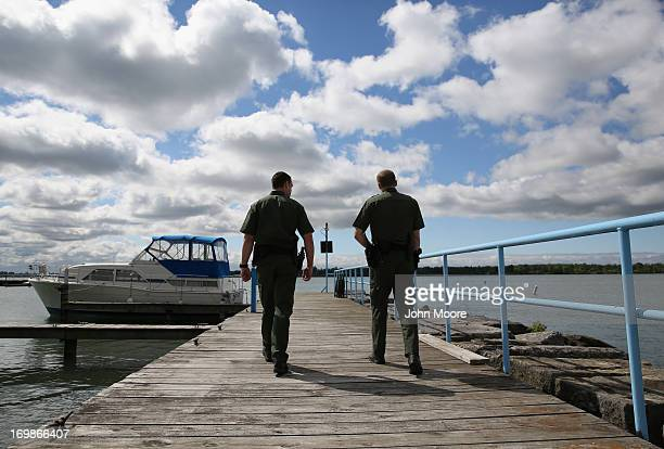 S Border Patrol agents walks along a marina on the Niagara River which forms the USCanada border on June 3 2013 in Beaver Island State Park New York...