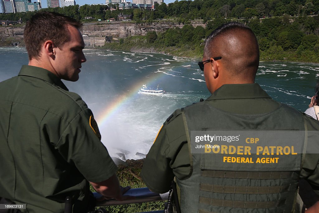 U.S. Border Patrol agents watch as a tourist boat rides through the mist of Niagara Falls on June 4, 2013 in Niagara Falls, New York. The major tourist attraction, which falls directly on the U.S.-Canada border, is a major destination for international visitors. Border Patrol agents detain travelers who have overstayed their visas as well as undocumented immigrants who attempt to illegally cross the international bridge in Niagara Falls.