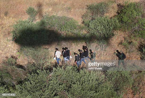 S Border Patrol agents with the help of helicopter pilots from the US Office of Air and Marine detain undocumented immigrants near the USMexico...
