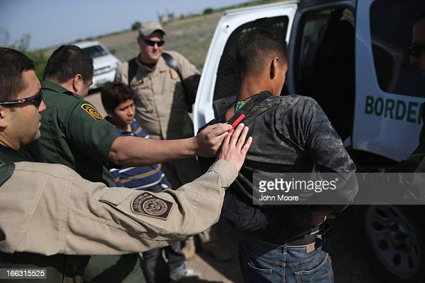 S Border Patrol and US Air and Marine agents work together to detain an undocumented immigrant after chasing him down near the USMexico border on...