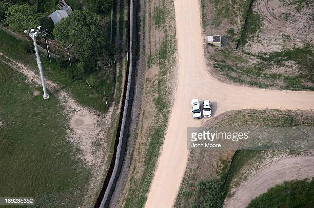 Border Patrol officers meet near a border fence and security camera tower near the USMexico border on May 21 2013 near Harlingen Texas The area...