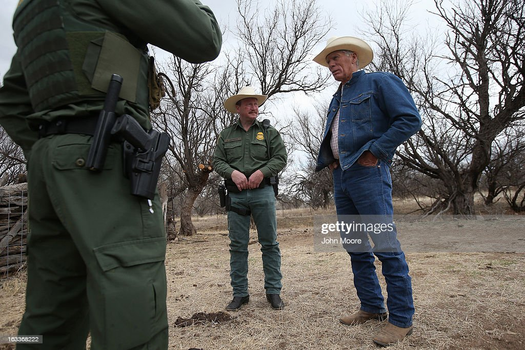 U.S. Border Patrol ranch liaison John 'Cody' Jackson (C) and a fellow agent meet with cattle rancher Ron Fish (R) near the U.S.-Mexico border on March 8, 2013 near Nogales, Arizona. Agent Jackson meets regularly with local ranchers to coordinate the agency's efforts on border issues, including drug smuggling and illegal immigration from Mexico.