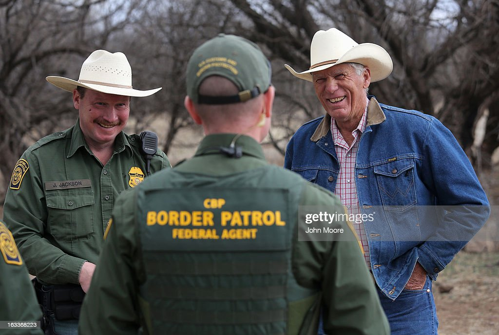 U.S. Border Patrol ranch liaison John 'Cody' Jackson (L) and a fellow agent meet with cattle rancher Ron Fish (R) near the U.S.-Mexico border on March 8, 2013 near Nogales, Arizona. Agent Jackson meets regularly with local ranchers to coordinate the agency's efforts on border issues, including drug smuggling and illegal immigration from Mexico.