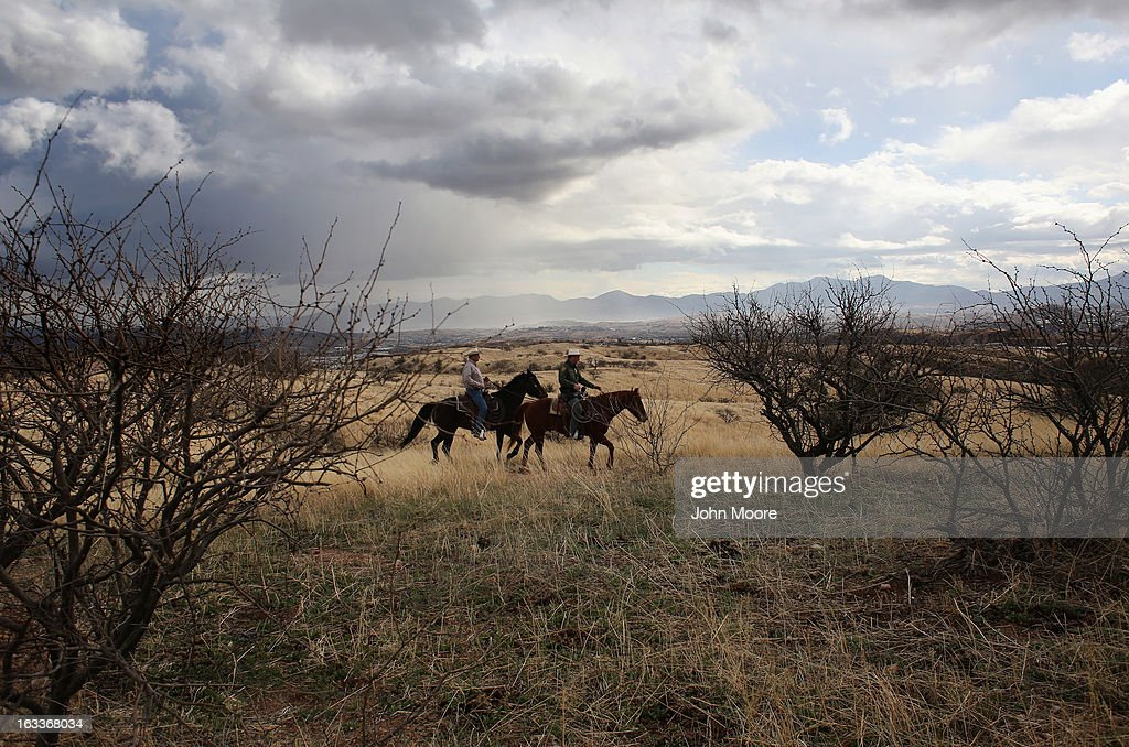 U.S. Border Patrol ranch liaison John 'Cody' Jackson (R) and cattle rancher Dan Bell ride through Bell's ZZ Cattle Ranch along the U.S.-Mexico border on March 8, 2013 in Nogales, Arizona. Agent Jackson meets regularly with local ranchers to coordinate the agency's efforts on border issues, including drug smuggling and illegal immigration from Mexico. Bell, a third generation rancher, grazes cattle on nearly ten miles of border property.