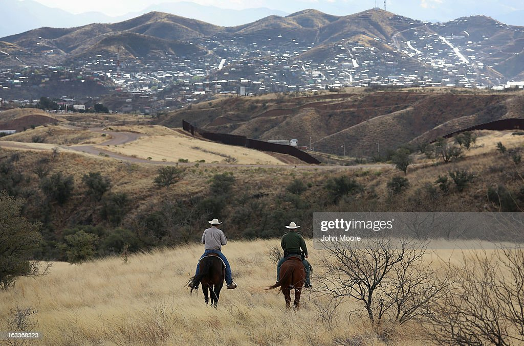 U.S. Border Patrol ranch liaison John 'Cody' Jackson (R) and cattle rancher Dan Bell ride through Bell's ZZ Cattle Ranch at the U.S.-Mexico border on March 8, 2013 in Nogales, Arizona. Agent Jackson meets regularly with local ranchers to coordinate the agency's efforts on border issues, including drug smuggling and illegal immigration from Mexico. Bell, a third generation rancher, grazes cattle on nearly ten miles of border property. Nogales, Mexico is seen on the far side of the border fence.