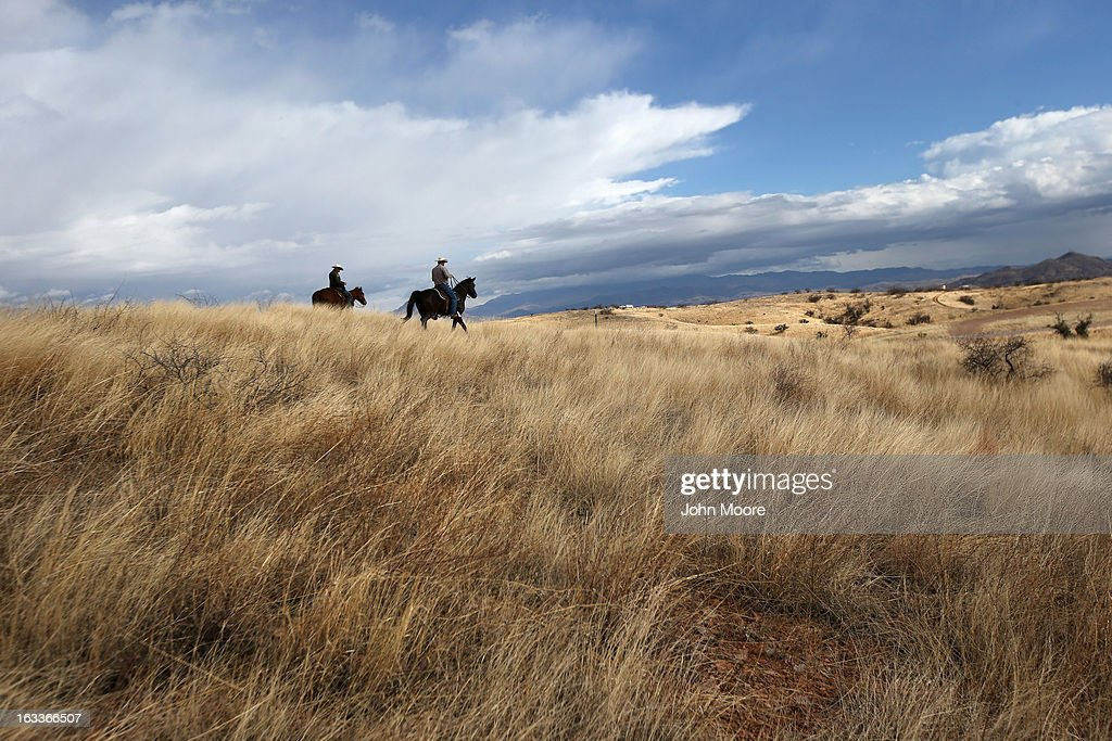 U.S. Border Patrol ranch liaison John 'Cody' Jackson (L) rides with cattle rancher Dan Bell on Bell's ZZ Cattle Ranch at the U.S.-Mexico border on March 8, 2013 in Nogales, Arizona. Agent Jackson meets regularly with local ranchers to discuss border issues, including drug smuggling and illegal immigration from Mexico. Bell, a third generation Arizona rancher, grazes cattle on nearly ten miles of border property.
