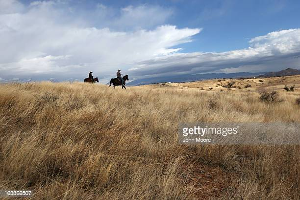 S Border Patrol ranch liaison John 'Cody' Jackson rides with cattle rancher Dan Bell on Bell's ZZ Cattle Ranch at the USMexico border on March 8 2013...