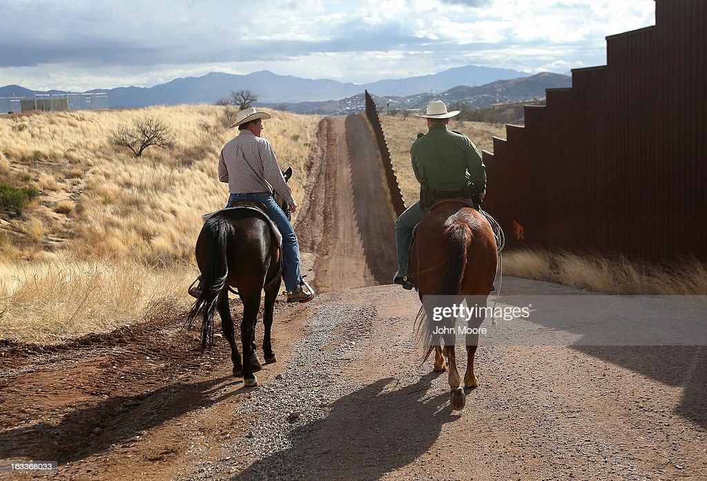 U.S. Border Patrol ranch liaison John 'Cody' Jackson (R) rides with cattle rancher Dan Bell on Bell's ZZ Cattle Ranch at the U.S.-Mexico border on March 8, 2013 in Nogales, Arizona. Jackson meets regularly with local ranchers to coordinate the agency's efforts on border issues, including drug smuggling and illegal immigration from Mexico. Bell, a third generation rancher, grazes cattle on nearly ten miles of border property.