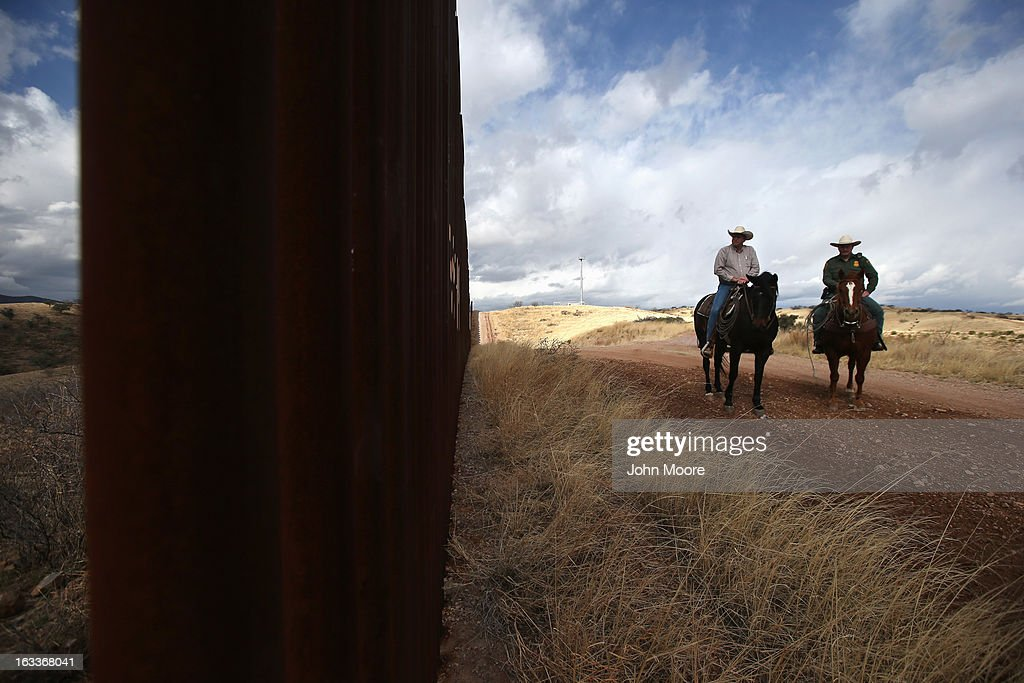 U.S. Border Patrol ranch liaison John 'Cody' Jackson (R) rides with cattle rancher Dan Bell on Bell's ZZ Cattle Ranch at the U.S.-Mexico border on March 8, 2013 in Nogales, Arizona. Agent Jackson meets regularly with local ranchers to coordinate the agency's efforts on border issues, including drug smuggling and illegal immigration from Mexico. Bell, a third generation rancher, grazes cattle on nearly ten miles of border property.