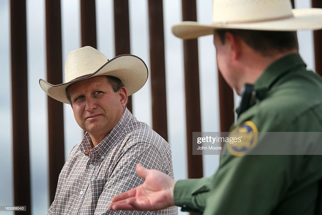 U.S. Border Patrol ranch liaison John 'Cody' Jackson (R) speaks with cattle rancher Dan Bell on Bell's ZZ Cattle Ranch at the U.S.-Mexico border fence on March 8, 2013 in Nogales, Arizona. Jackson meets regularly with local ranchers to coordinate the agency's efforts on border issues, including drug smuggling and illegal immigration from Mexico. Bell, a third generation Arizona rancher, grazes cattle on nearly ten miles of border property.