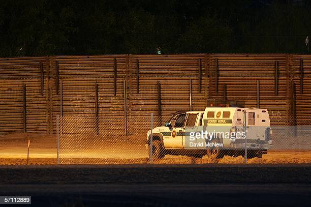 A border patrol vehicle keeps watch over a barren zone of graded earth and metal fences separating the US and Mexico on March 16 2006 near the border...