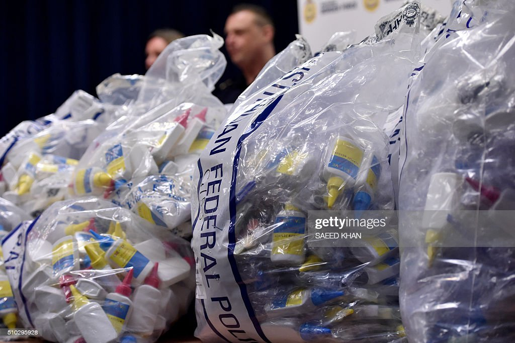 Border Police officers stand next to a haul of crystal methamphetamine concealed in packaging at the Australian Federal Police headquarters in Sydney on February 15, 2016. Australian police have seized more than 712 million USD in crystal methamphetamine, or ice, some concealed in gel bra inserts in one of the country's biggest drug busts. AFP PHOTO / Saeed KHAN / AFP / SAEED