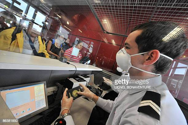 A border policeman wearing protective mask and gloves controls passports of passengers arriving from Mexico at the RoissyCharles de Gaulle airport...