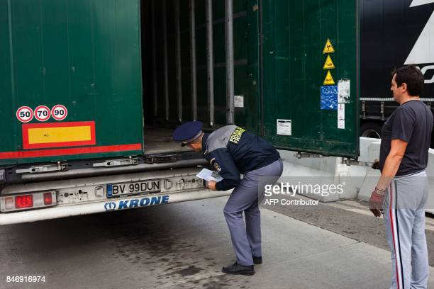 A border policemen checks a lorry in Nadlac western Romania at the border crossing to Hungary on September 12 2017 Families of migrants landing on...