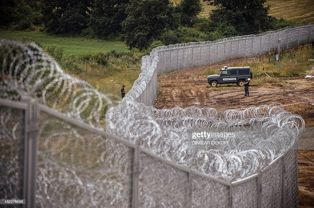 Border policemen stand guard next to a barbed wire wall on the Bulgarian border with Turkey, near the village of Golyam Dervent on July 17, 2014. Overwhelmed by an influx of mostly Syrian immigrants, Bulgaria has taken steps to secure its EU border -- including building a barbed-wire fence -- but now faces criticism from rights groups. The 30-kilometre (19-mile) fence, standing three metres (10 feet) high and fortified with razor wire coils, was completed this week. Covering the least visible section of Bulgaria's 275-kilometre (170-mile) border with Turkey, it aims to stem a flow of refugees that saw more than 11,000 people enter the country illegally last year -- 10 times the annual figure before the Syrian conflict.