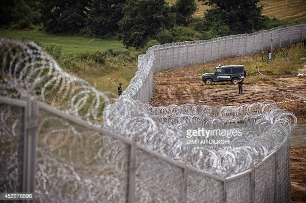 Border policemen stand guard next to a barbed wire wall on the Bulgarian border with Turkey near the village of Golyam Dervent on July 17 2014...