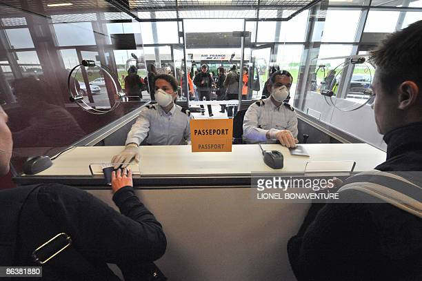Border policemen wearing protective masks and gloves control passports of passengers arriving from Mexico at the RoissyCharles de Gaulle airport...