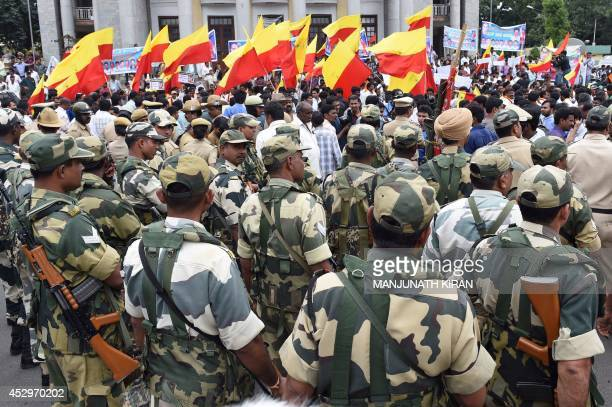Border Security Force personnel keep a watch as proKannada activists stage a demonstration calling for the shutdown of the city in protest against...