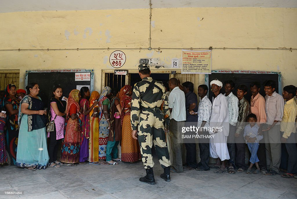 A Border Security Force personnel keeps vigil as people queue to cast their votes in the state assembly elections at Sanand town, some 30 kms from Ahmedabad on December 13, 2012. The first phase of voting in state assembly elections in the western Indian state of Gujarat has begun with the next phase on December 17, 2012. AFP PHOTO/Sam PANTHAKY
