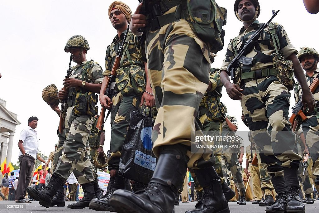 Border Security Force (BSF) personnel march as pro-Kannada activists stage a demonstration calling for the shutdown of the city in protest against the rising crimes against women and children in Bangalore on July 31, 2014. About 50-pro-Kannada organisations took out a protest rally from Town Hall to the state secretariat in the city centre and submitted a memorandum to Karnataka Chief Minister Siddaramaiah to check crimes against women and urging him to take stringent action against the perpetrators. AFP PHOTO/Manjunath KIRAN