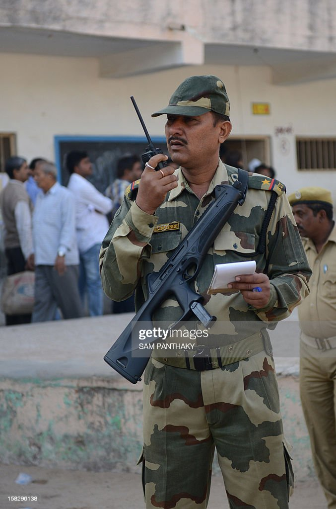 A Border Security Force personnel monitors as people queue to cast their votes in the state assembly elections at Sanand, some 30 kms from Ahmedabad on December 13, 2012. The first phase of voting in state assembly elections in the western Indian state of Gujarat has begun with the next phase on December 17, 2012. AFP PHOTO/Sam PANTHAKY