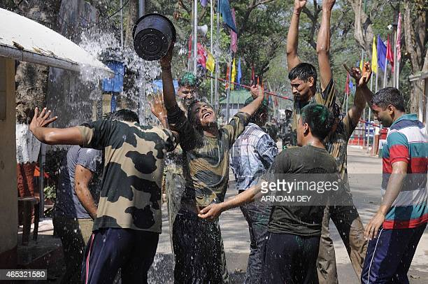 Border Security Force personnel splash water as they celebrate Holi at the India/Bangladesh checkpost of Akhaura at Agartala the capital of...