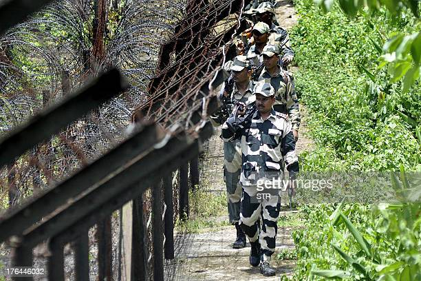 Border Security Force personnel walk along the IndiaBangladesh fencing area during a routine patrol prior to the upcoming 67th Independence Day near...