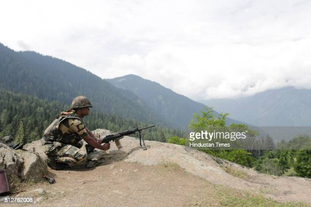 Border Security Force soldier stands guard on a mountain on July 11 2017 in Chandanwari around 116 kilometers south of Srinagar India Seven pilgrims...