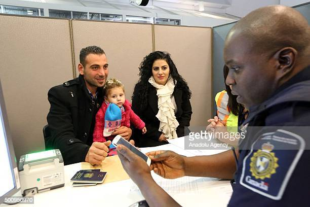 Border Services Officer BoakyeCotie processes a Syrian refugee family at Toronto Pearson International Airport on December 11 2015