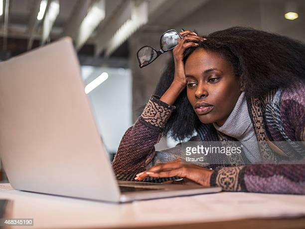 Bored African American woman surfing the Internet.